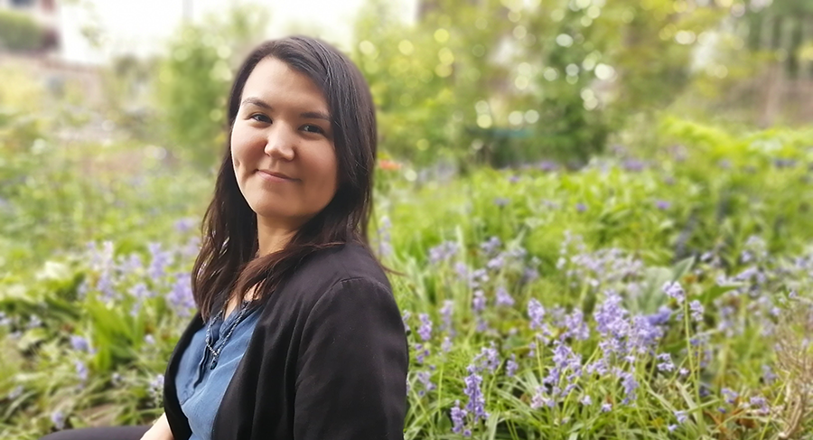 Inuk editor Rachel Taylor is shown from the waist up. She is smiling in a garden, wearing a black blazer and blue top.